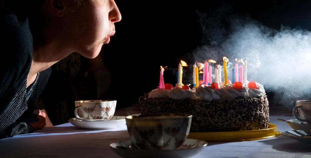 young woman is blowing out candles on cake